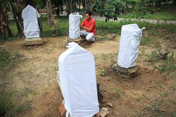mengafani nisan kuburan