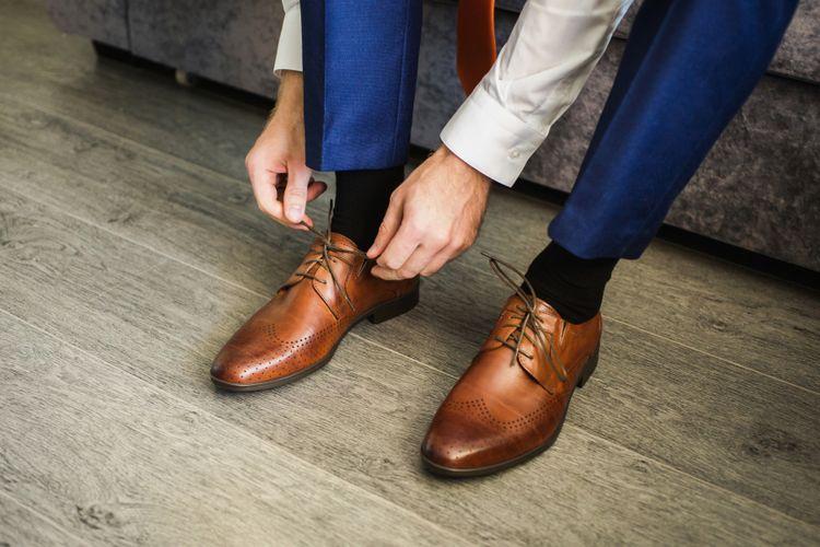 memakai sepatu atau sandal sambil berdiri